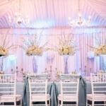 Pink and grey head table with uplights, chandeliers, white Chivari chairs and stunning tall spraying floral centerpieces and candelabras