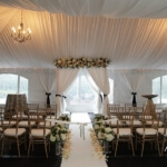 Azzura Photography logo with a beautiful wedding ceremony tent setup in white, blush and ivory and gold Chivari chairs