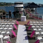 Waterways Cruises wedding ceremony at their pier with vivid pink parasols and white chairs
