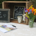 Guest sign in with chalkboards and bright floral arrangement