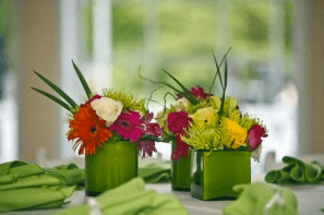Centerpiece vases of flowers in chartreuse green with vibrant florals